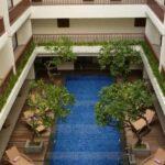 Kolam renang yang terletak di tengah-tengah diantara susunan kamar-kamar hotel