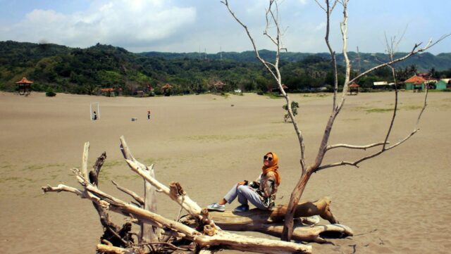 foto dengan latar belakang hamparan pasir