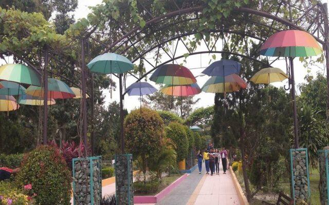 Area taman dengan payung aneka warna tergantung di Taman Buah Lubuk Pakam