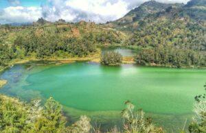 panorama bukit dan danau berwarna hijau toska