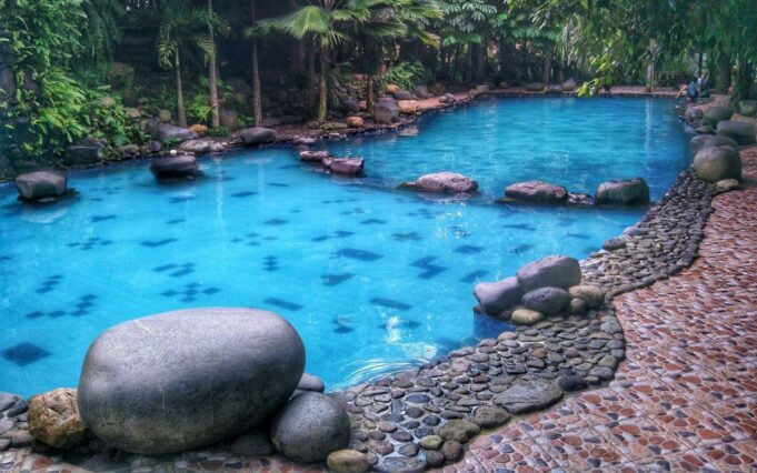 kolam renang dikelilingi taman hijau watu gunung