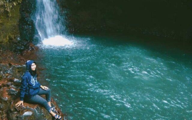 Berfoto berlatar air terjun dan kolam hijau