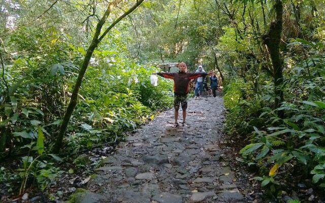 Jalur treking menuju Curug Cibeureum Bogor merupakan jalan berbatu dengan pepohonan di kiri-kanan jalan