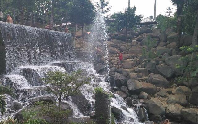 Mandi dan bermain air di bawah guyuran air terjun buatan