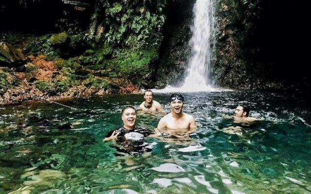 Pengunjung sedang berenang di cerukan bawah air terjun