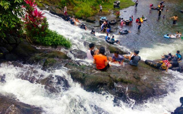 pengunjung berenang di air terjun