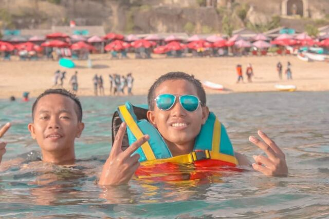 wisatawan yang sedang berenang di pantai pandawa