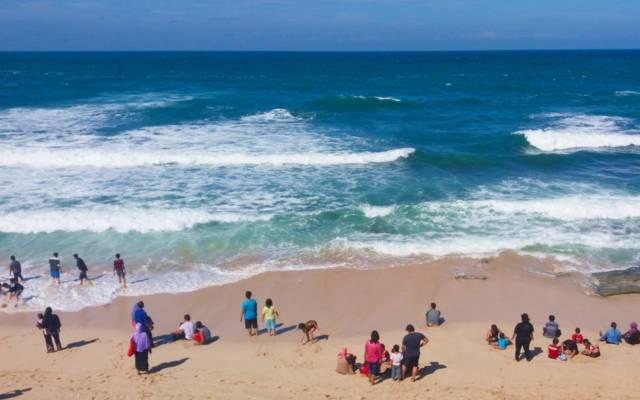wisatawan sedang bermain di tepi pantai