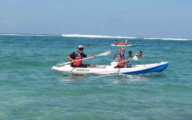 wisatawan bermain kano di kawasan pantai
