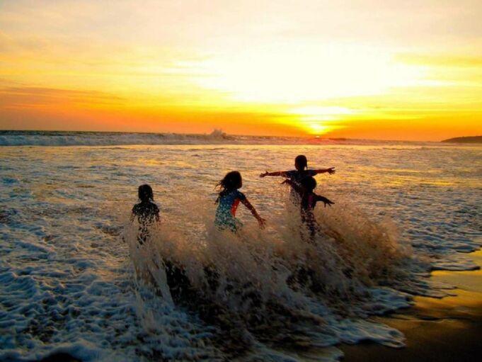 bermain air dan pasir di area pantai sawarna