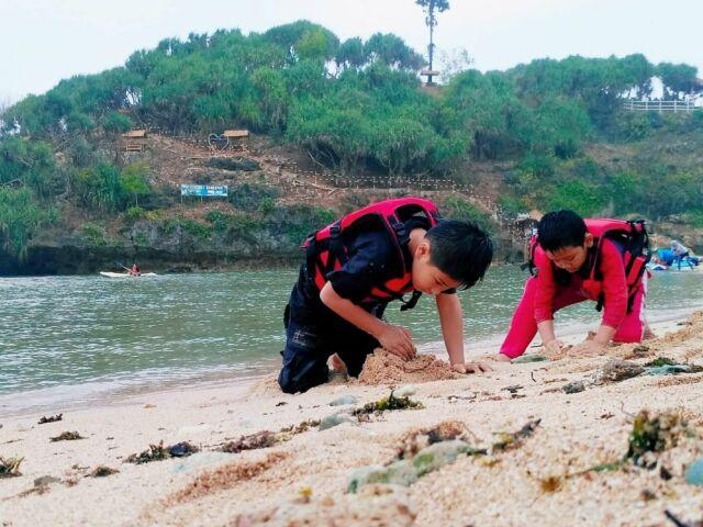 pengunjung sedang bermain air dan pasir di pantai