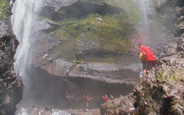 wisatawan yang sedang mandi dan berenang di air terjun