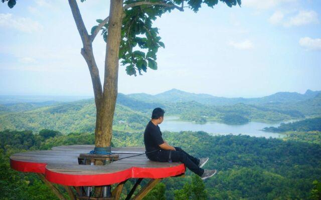 gardu pandang foto berlatar gunung dan jurang di area wisata kalibiru
