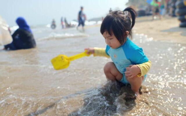 anak-anak sedang bermain pasir di tepi pantai