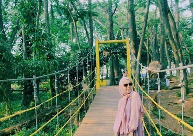 berfoto dengan latar berbagai ornamen di taman