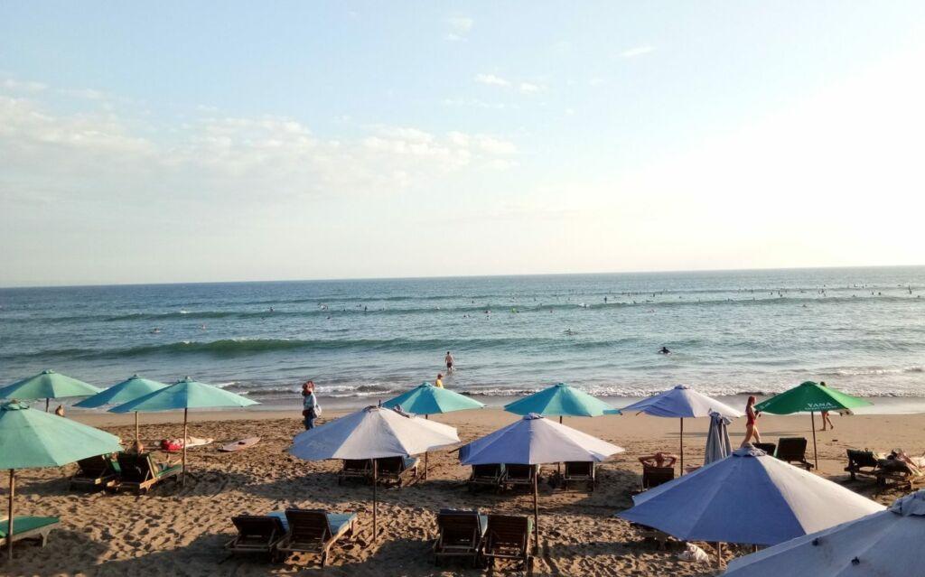 Pengunjung Menikmati Berjemur di Tepi Pantai