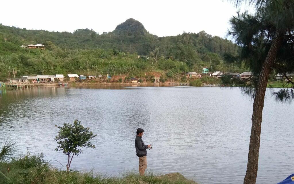 Pengunjung memancing di danau