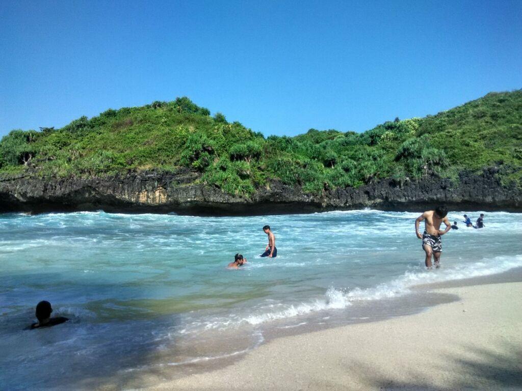 Para Pengunjung sedang Bermain di Pantai Sedahan