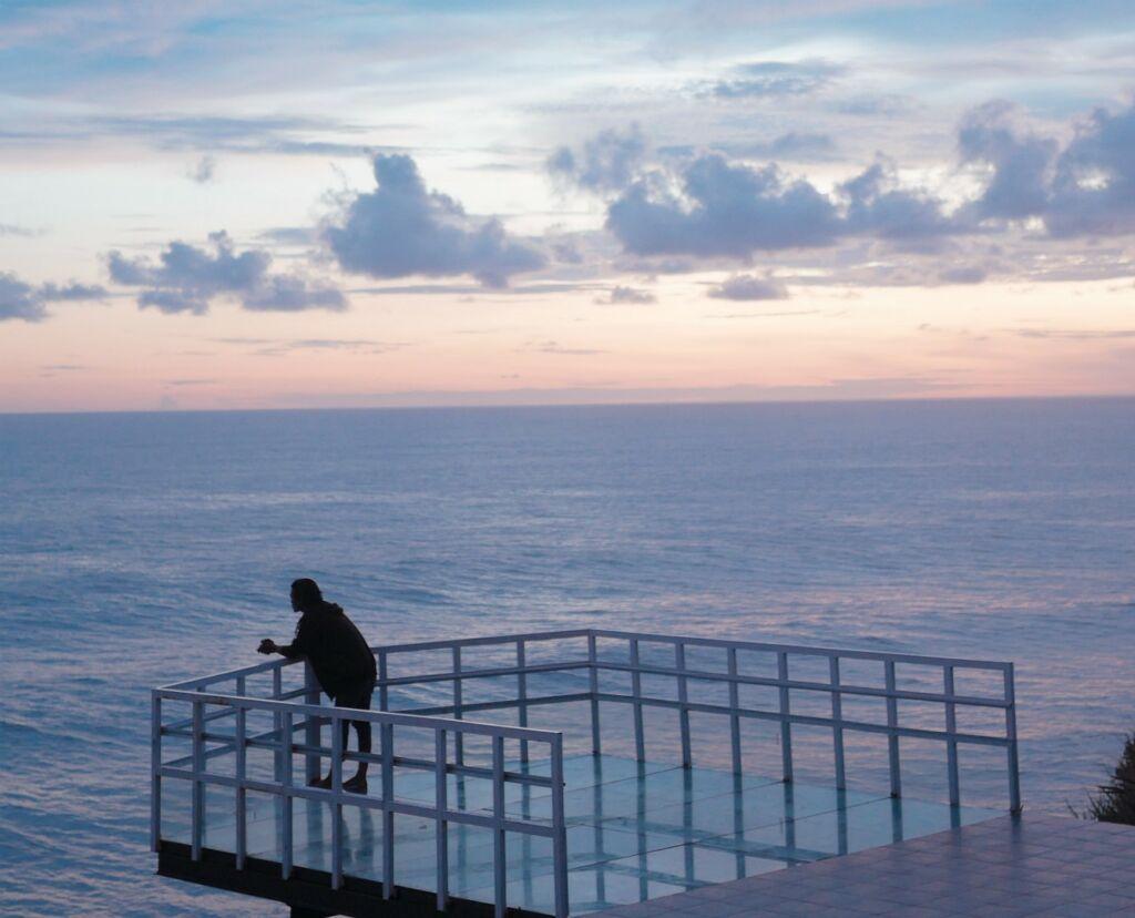 Berdiri di tepi lautan lepas saat senja