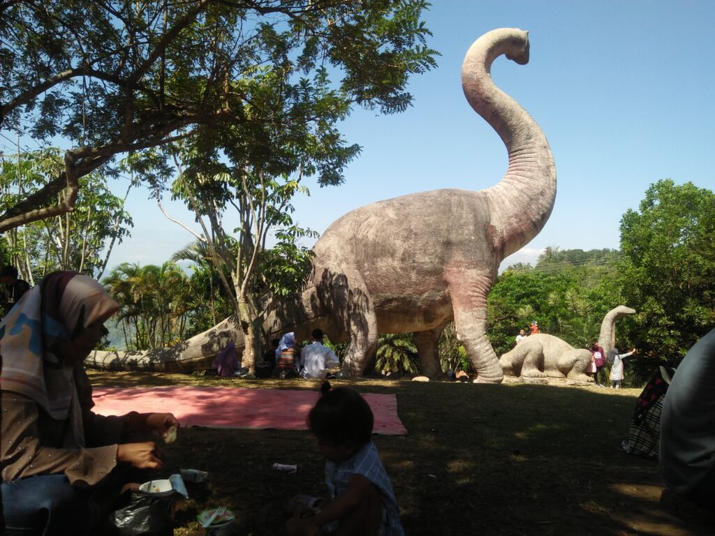 pengunjung sedang berpiknik di taman dinosaurus