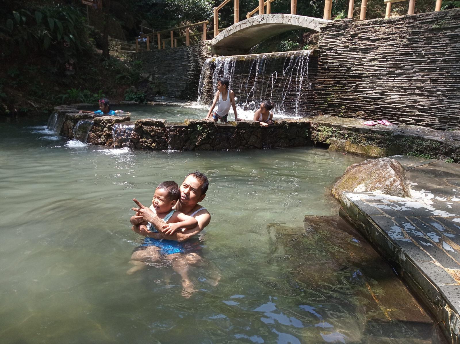 Berenang di kolam air alami