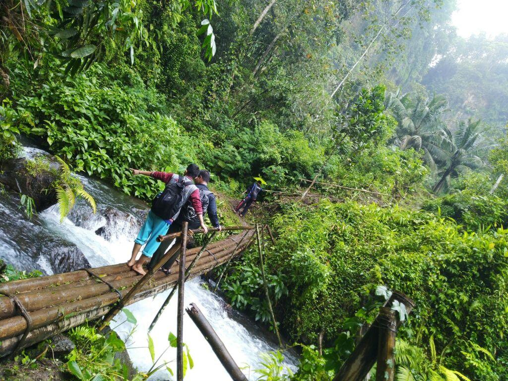 Pengunjung melewati jembatan bambu