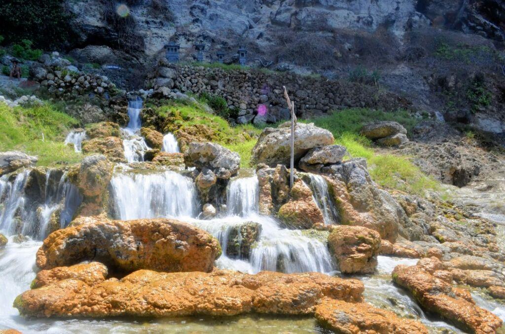 Air Terjun Seganing Klungkung Bali dikelilingi batu-batu cadas berwarna kuning kecoklatan - Bliyan Aryana