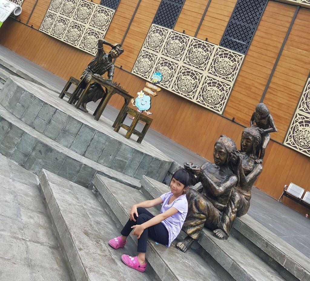 wisatawan sedang berfoto dengan ornamen dan patung-patung