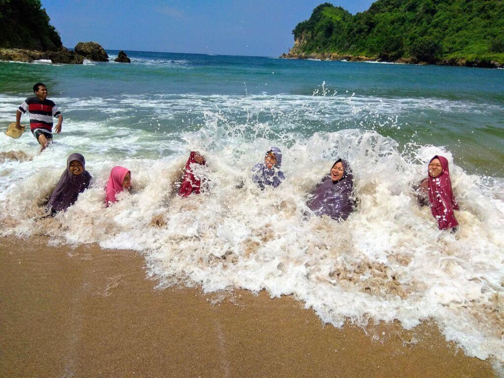 bermain air dengan deburan ombak tepi pantai