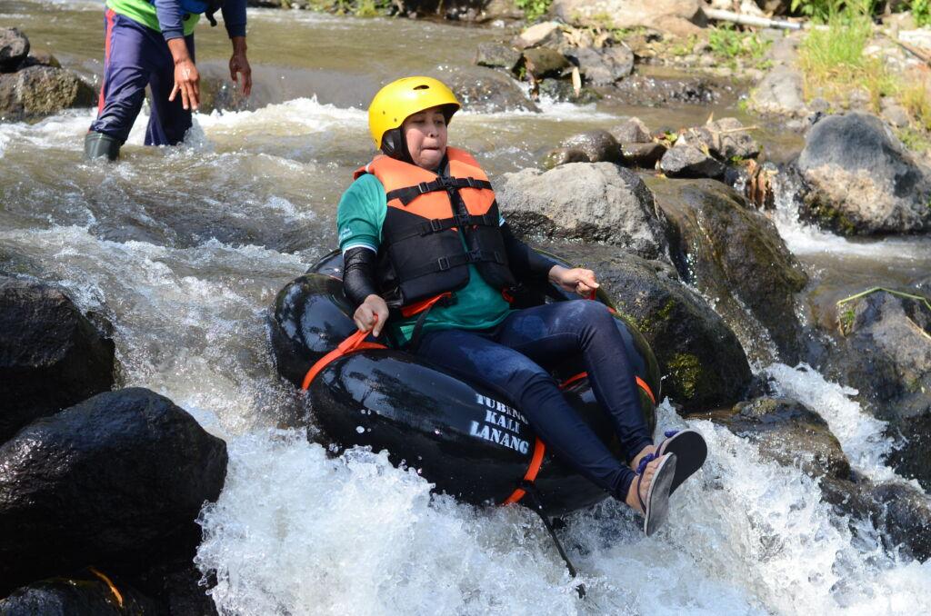 bermain river tubing di sungai yang mengalir di area taman