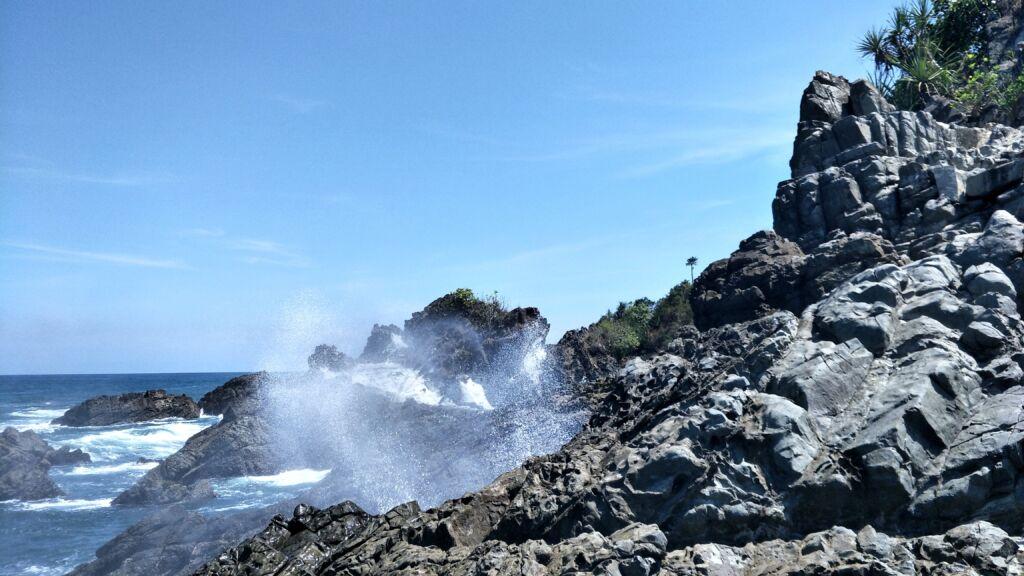 Ombak yang Menghantam Bukit Karang di Pantai Lampon. Foto: Google Maps / Jujjuu