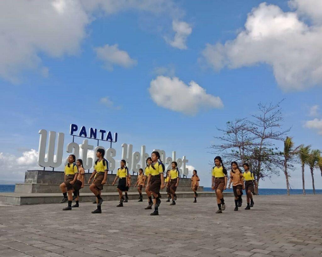 Siswa sekolah dasar melakukan gerak jalan di pedestrian Pantai Wates Karangasem Bali