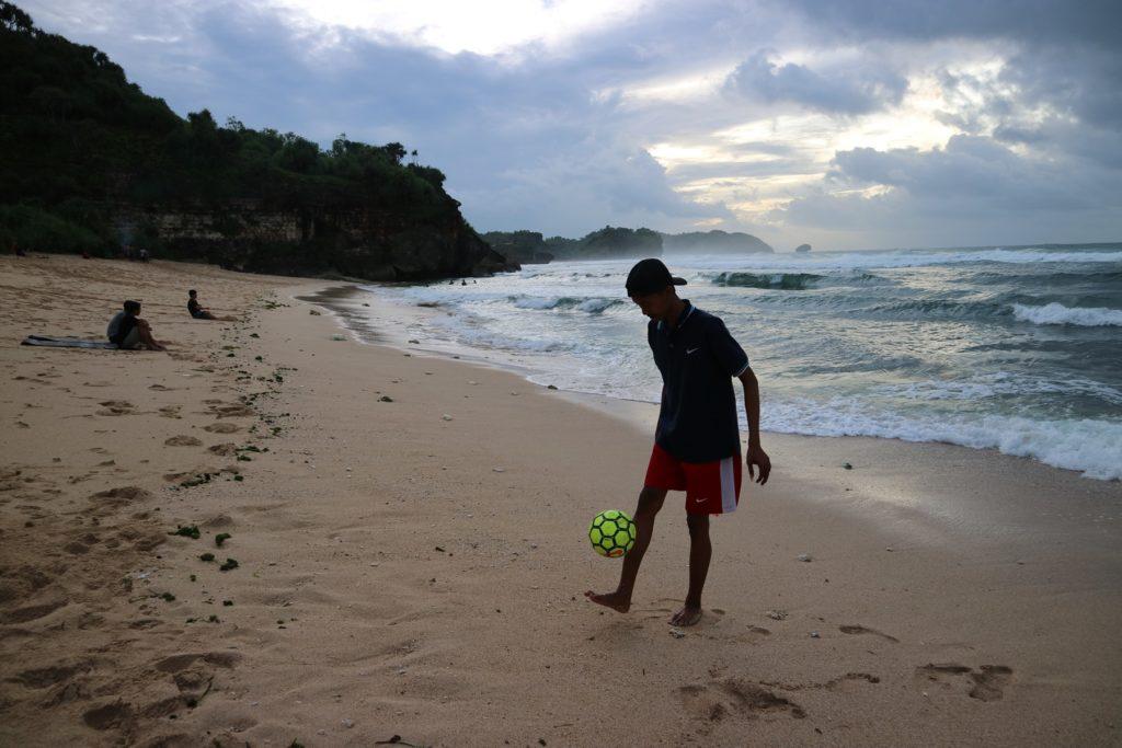 Bermain bola di tepi pantai