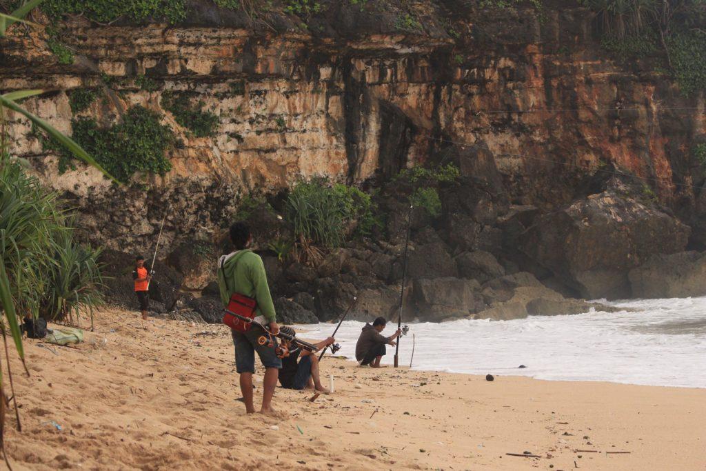pengunjung sedang memancing di sekitar pantai