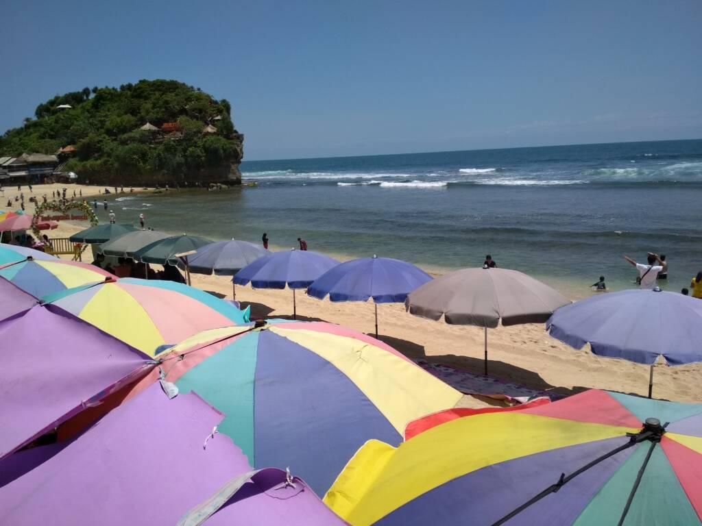 kursi-kursi dan payung pantai tempat bersantai