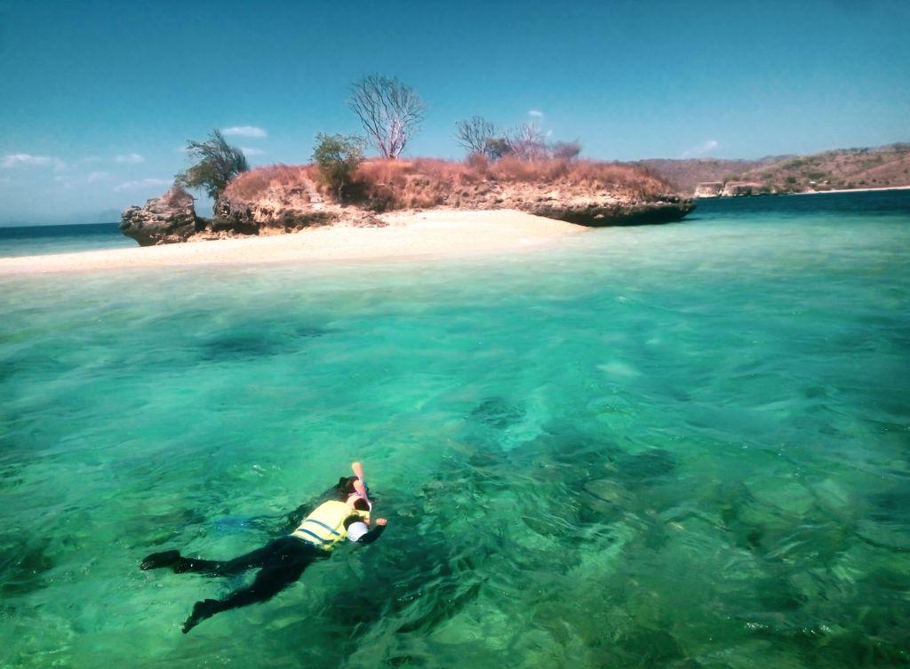 wisatawan sedang melakukan snorkeling di sekitar pantai