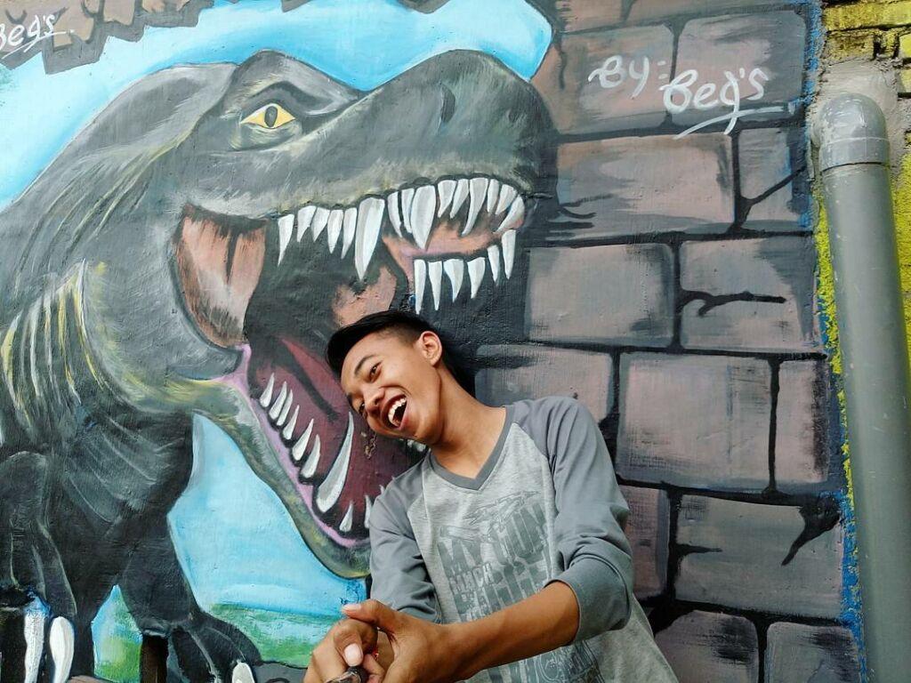 Berfoto dengan Mural Dinosaurus di Kampung Tridi Malang. Foto: instargram / babangirman