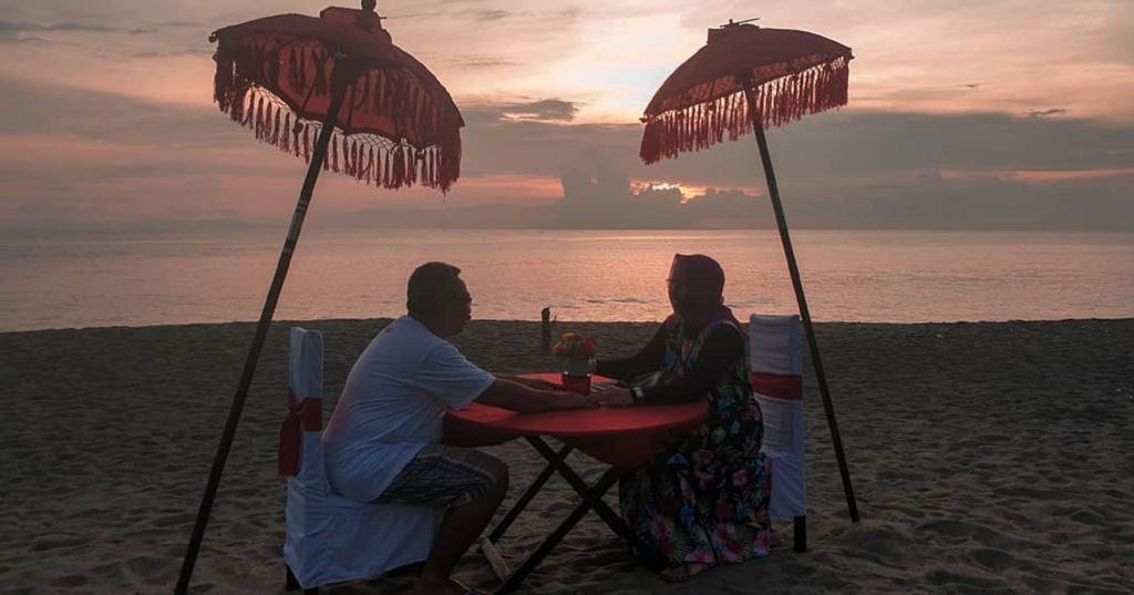 Menikmati romantisnya suasana momen terbenamnya matahari di cakrawala laut Pantai Senggigi Lombok Barat NTB - koko_brengs