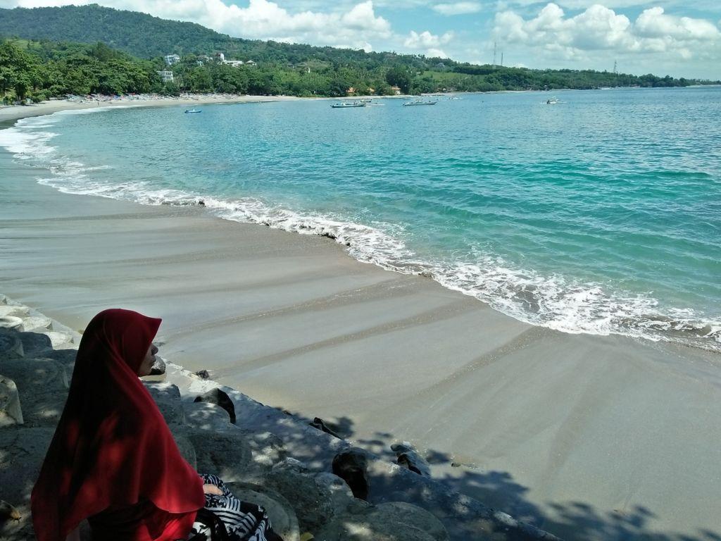 Pasir putih dengan gradasi warna laut yang memukau menjadi dan jajaran bukit menghijau
