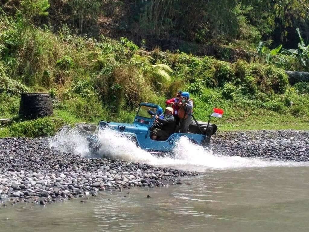 Jeep melewati kubangan air pinggir sungai