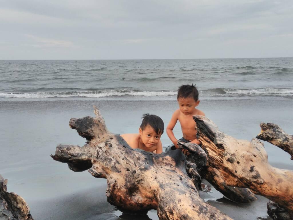 Anak - anak yang Asyik Bermain di Tepi Pantai