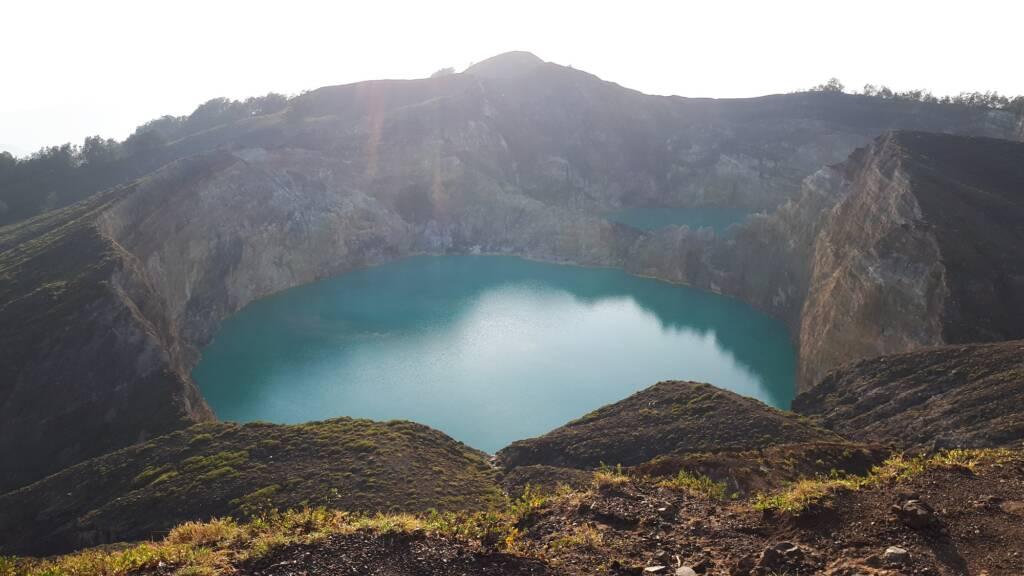 Bentang alam perbukitan yang mengapit danau hijau toska