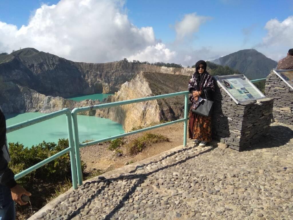 Pengunjung sedang Berpose dengan Latar Belakang Danau Kelimutu