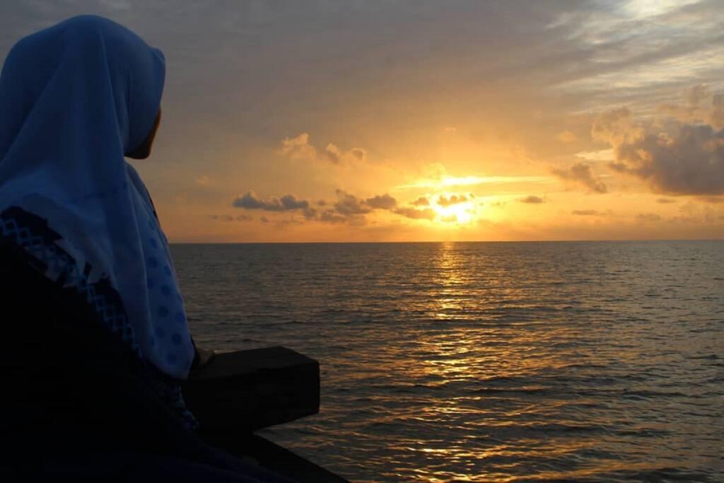 menikmati matahari terbenam di pantai pulau berhala