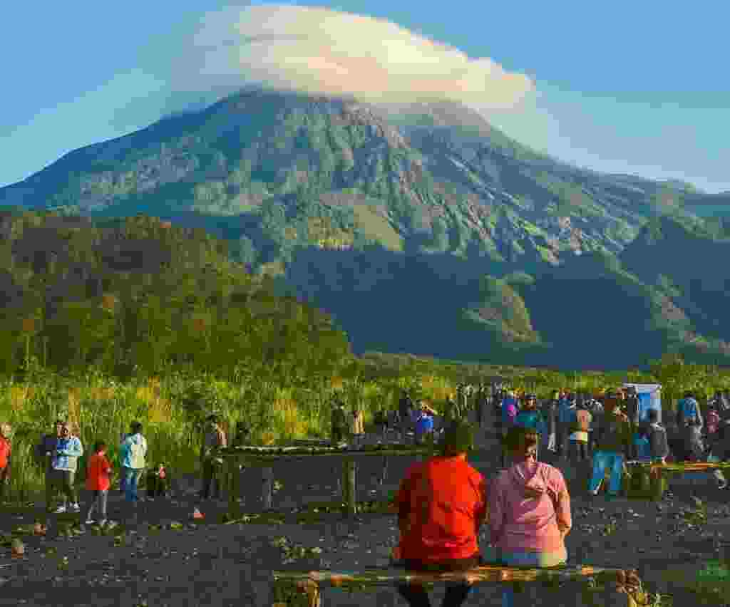 wisatawan sedang bersantai dan menikmati keindahan gunung merapi
