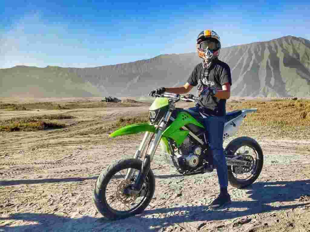 wisatawan mengendarai motor trail di lautan pasir