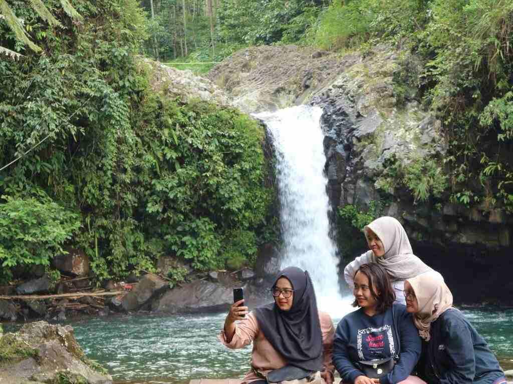 Pengunjung Tampak Mengabadikan Momen di depan Air Terjun