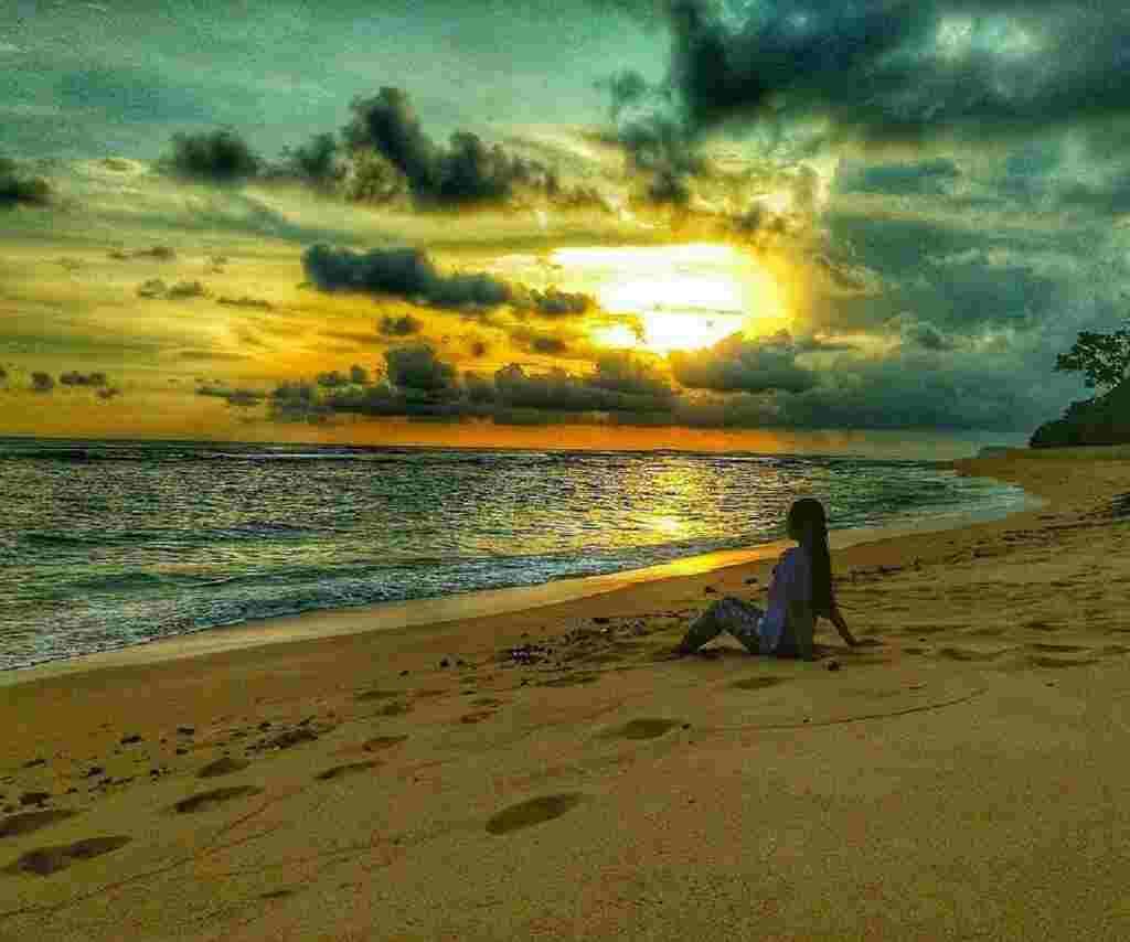 wisatawan menikmati sunset di tepi pantai