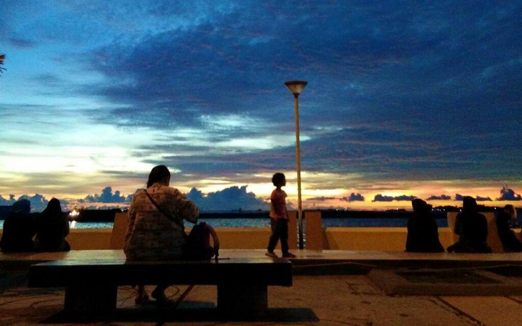 wisatawan bersantai di tepi pantai