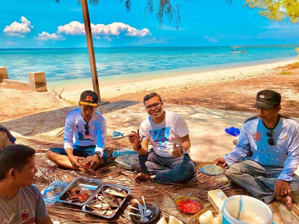pengunjung sedang makan di tepi pantai